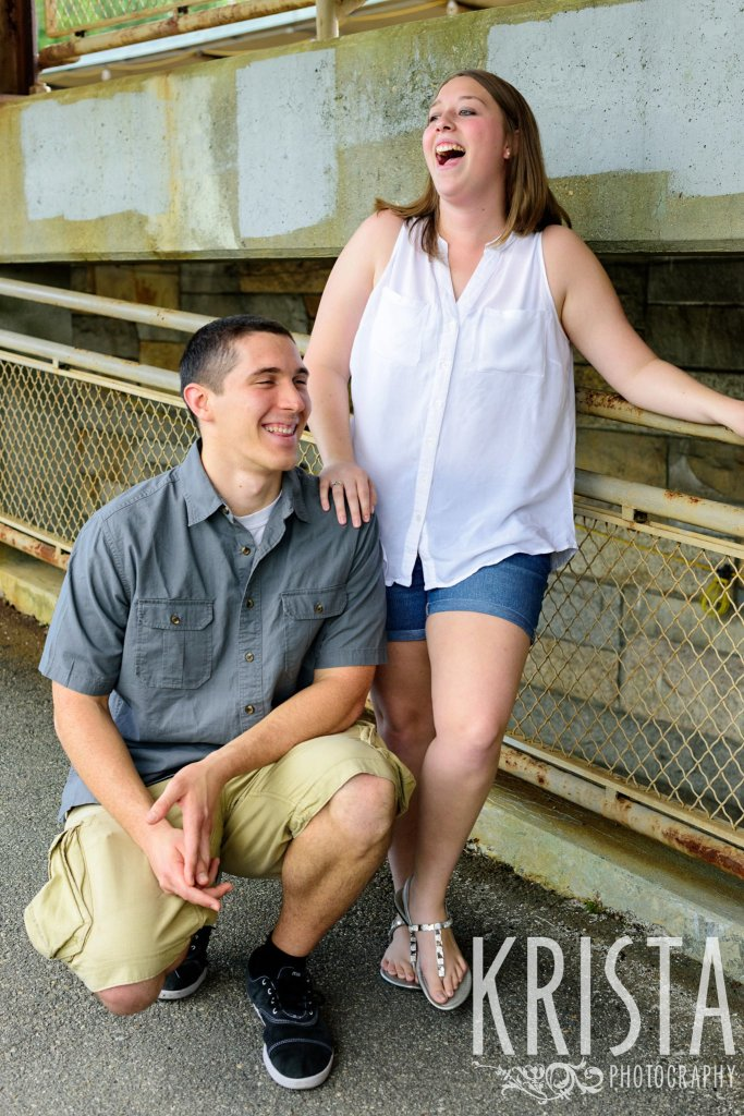 engaged couple laughing on overpass during family portrait session
