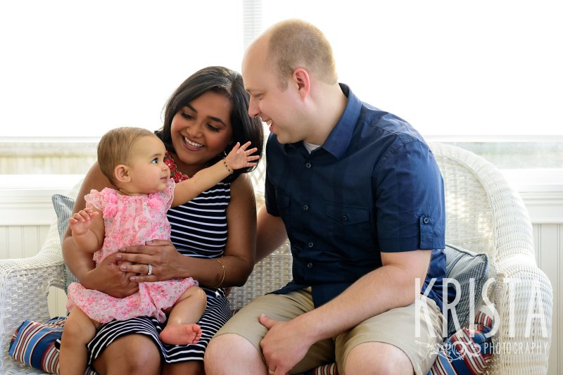 adorable family of mom dad and baby girl on couch of home during lifestyle portrait session