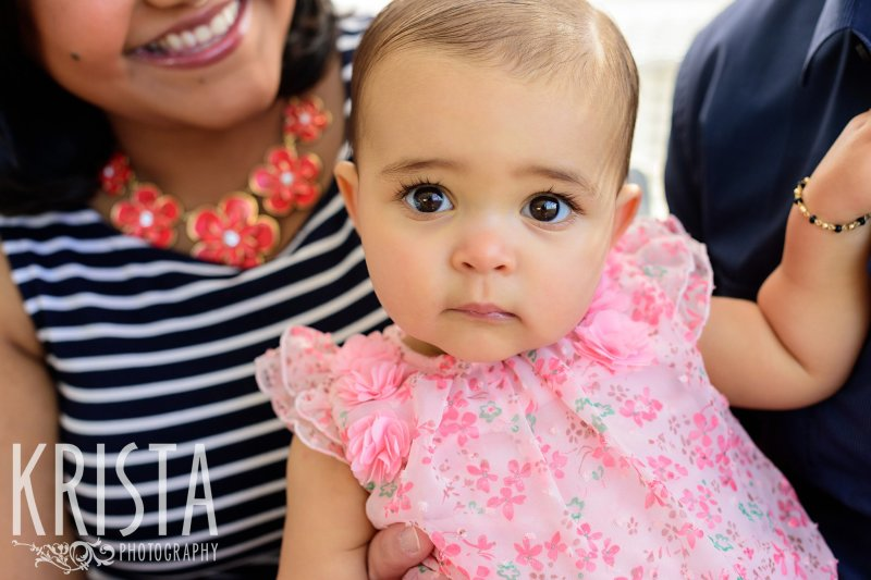 adorable baby girl in pink floral romper on mom's lap during lifestyle portrait session at home