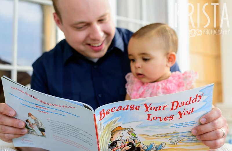 "adorable baby girl on dad's lap reading ""Because Your Dad Loves You"" during lifestyle portrait session at home"