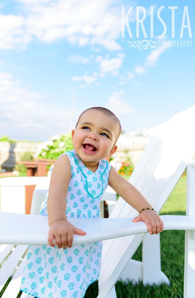 gorgeous happy baby girl standing on white adirondack chair in turquoise blue patterned dress