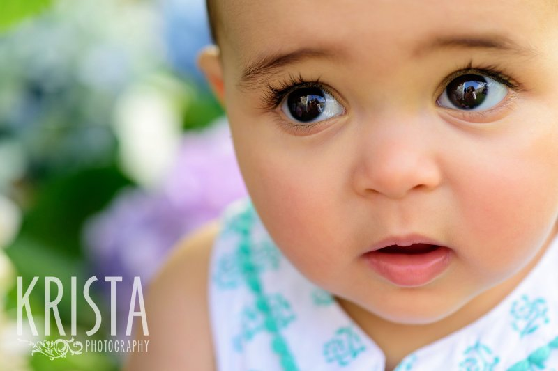 gorgeous brown eyed baby girl in turquoise patterned dress during lifestyle portrait session on Cape Cod