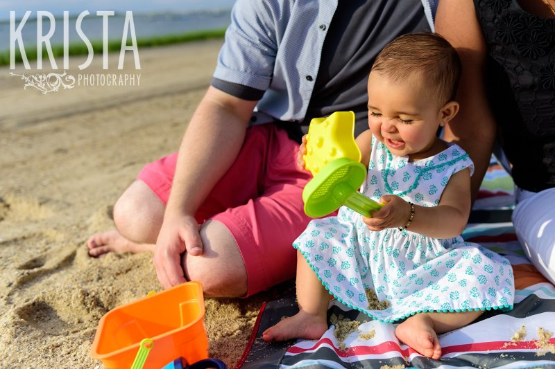 baby girl in turquoise patterned dress hitting beach shovels together on Cape Cod during lifestyle portrait session