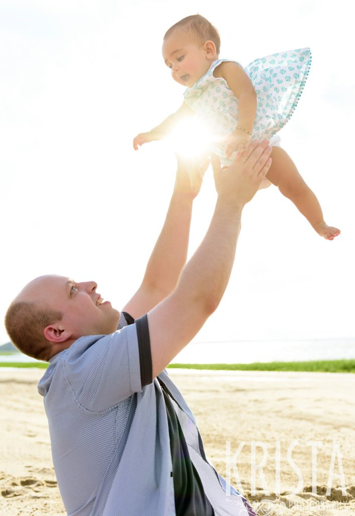 dad tossing baby girl into sunset sky on beach of Cape Cod during lifestyle portrait session
