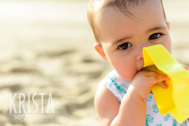 beautiful brown eyed baby girl chewing on sand toy on beach of Cape Cod during lifestyle portrait session