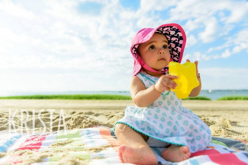 adorable baby girl in turquoise patterned dress with pink sun hat playing in sand of beach on Cape Cod during lifestyle portrait session
