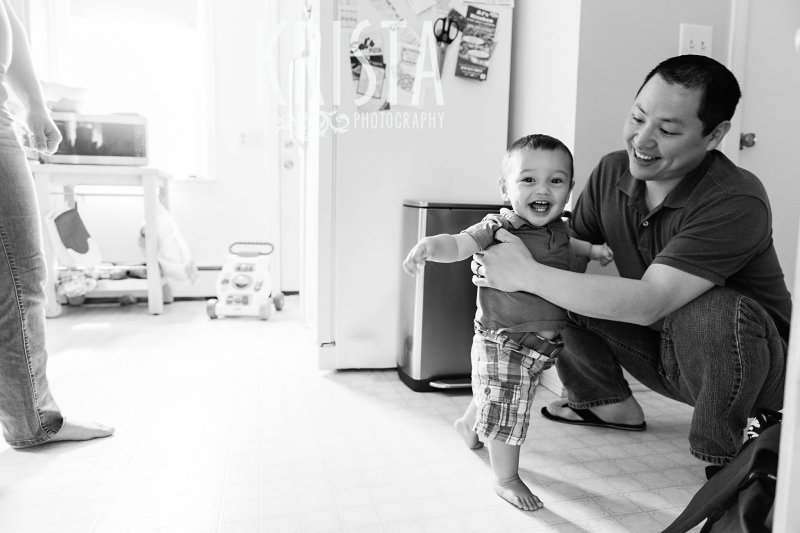 black and white image of one year old baby boy learning to walk with his dad in the kitchen