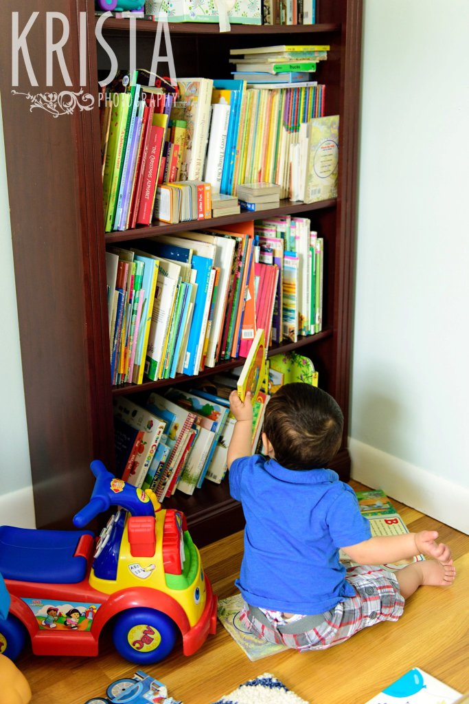 one year old baby boy in blue collared shirt taking book off of bookshelf during lifestyle portrait session at home