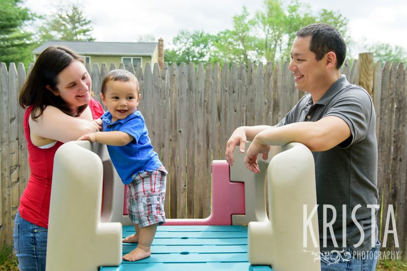 one year old baby boy standing on play slide in backyard during lifestyle portrait session at home