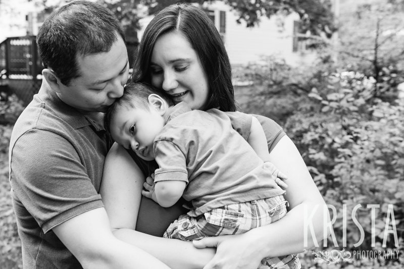 black and white image of parents with one year old son snuggling into mother during lifestyle portrait session at home