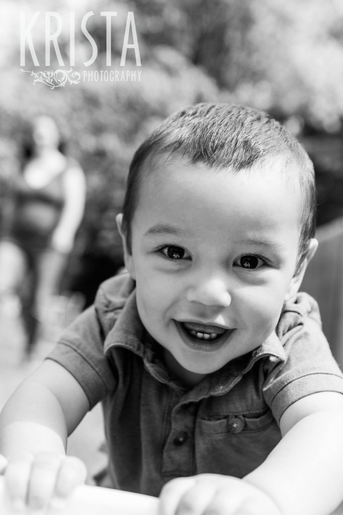 black and white image of one year old boy smiling a big toothy smile during lifestyle portrait session at home
