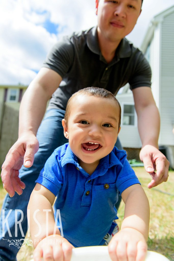 one year old baby boy with tongue hanging out during lifestyle portrait session at home in backyard