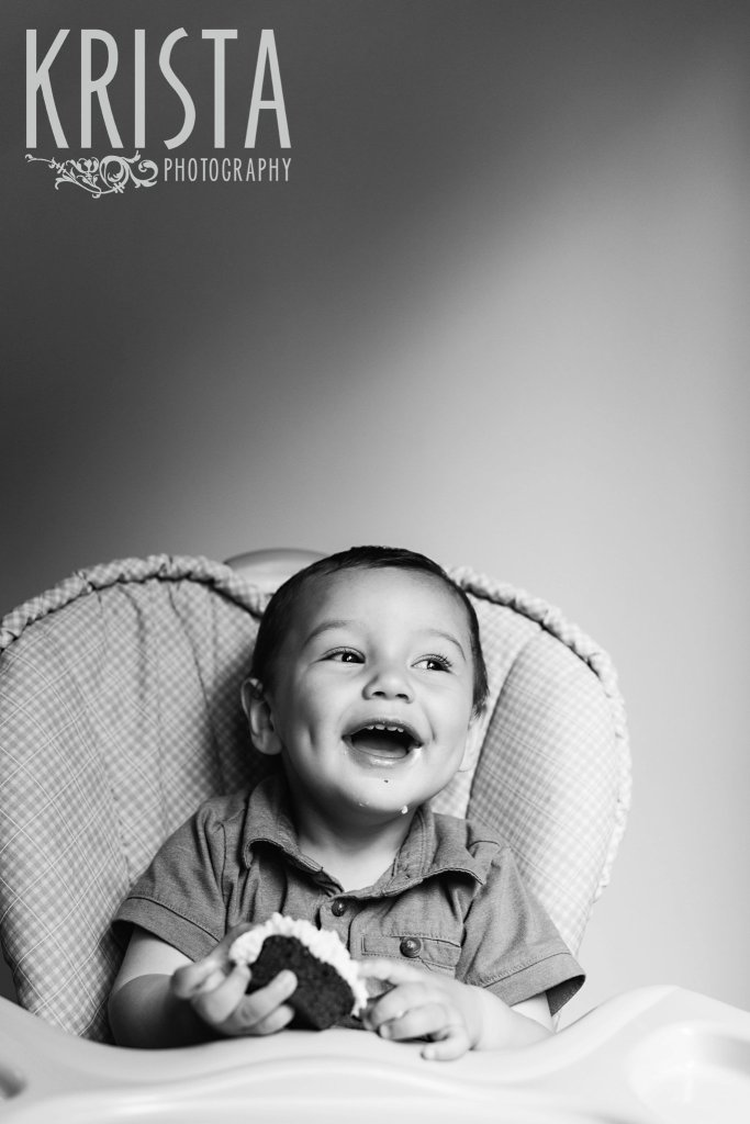 black and white image of one year old baby boy in highchair having first birthday cake during lifestyle portrait session