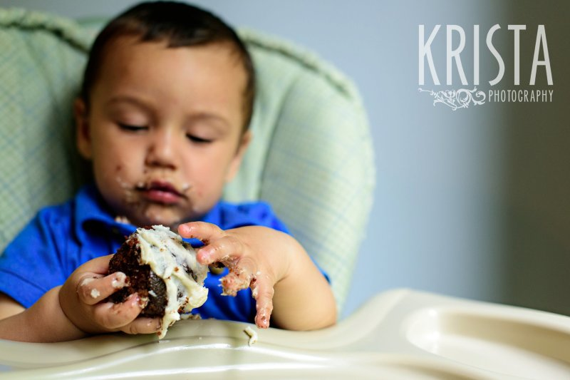one year old birthday boy trying cake for first time during lifestyle portrait session at home