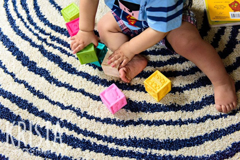 first birthday baby boy feet playing with blocks on white and blue carpet during lifestyle portrait session at home