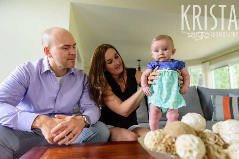family with three month old baby girl in blue aqua and yellow dress in home during lifestyle portrait session