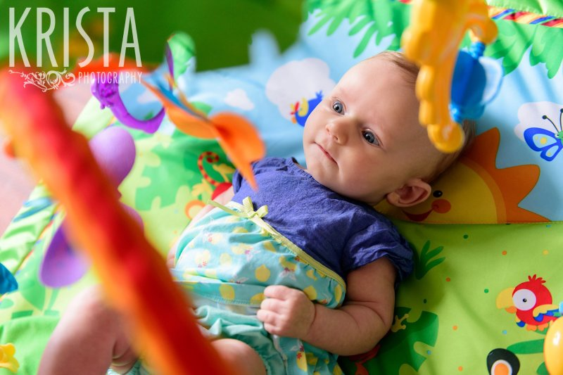 three month old baby girl laying on back under play set staring a toys during lifestyle portrait session at home