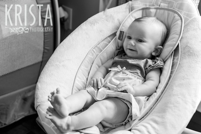 black and white image of three month old baby girl sitting in swing grinning with ankles crossed during lifestyle portrait session at home.