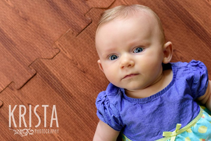 serious three month old baby girl laying on back on wood floor during lifestyle portrait session at home
