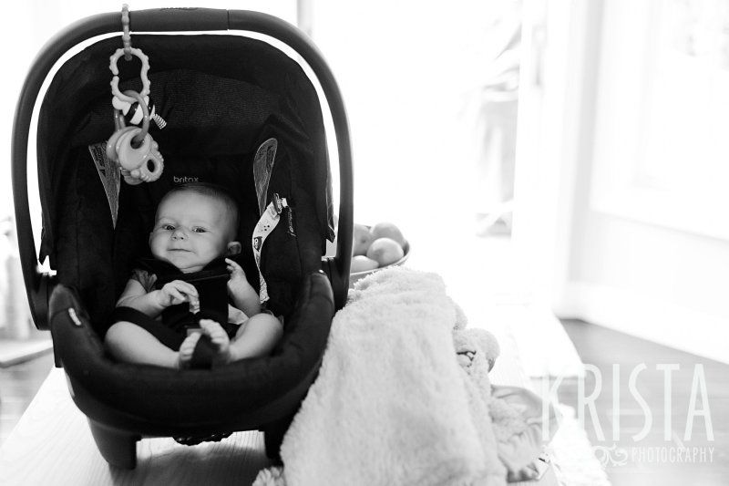 black and white image of three month old baby girl in carseat at home during lifestyle portrait session at home