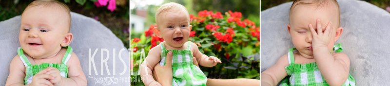 smiley and sleepy three month old baby girl in green gingham sundress in front of red flowers during lifestyle portrait session at home