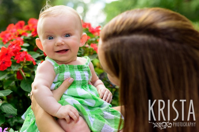 mother from behind holding three month old baby girl in green gingham sundress who is smiling during lifestyle portrait session at family home