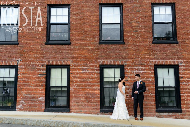 bride and groom in front of brick wall © Krista Photography