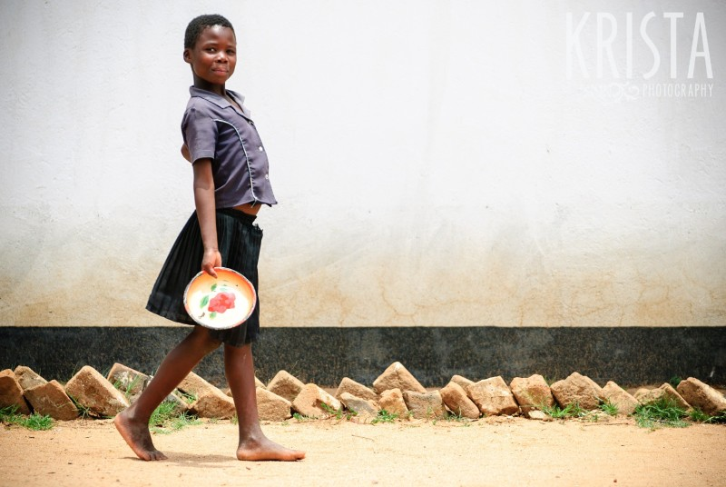 A girl in rural Zimbabwe carries a plate to get her free lunch at school. Krista Guenin | Humanitarian Photographer