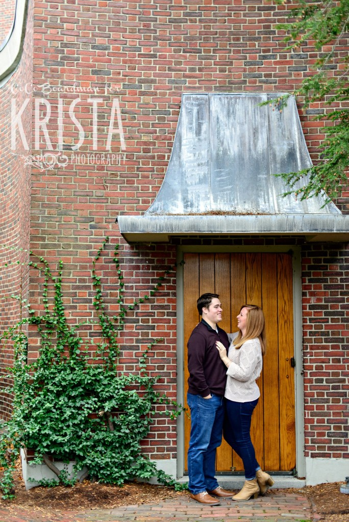 couple snuggling under a metal awning at St. Anselm College - Saint Anselm Engagement
