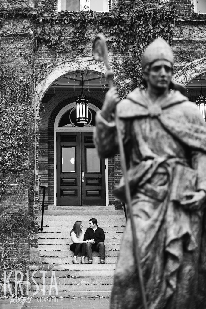 couple sitting on the steps behind statue at St. Anselm College - Saint Anselm Engagement